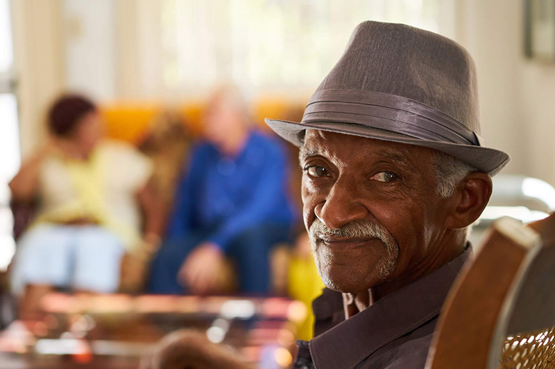 older gentleman in a hat looking at the camera