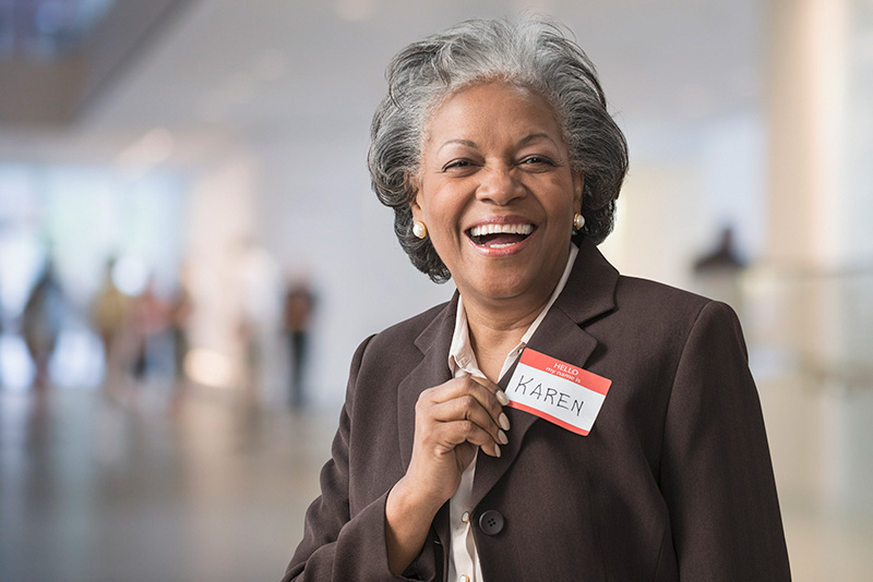 woman smiling at the camera with a name tag on her jacket