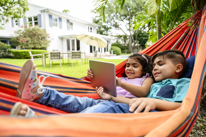 two kids in a hammock looking at a tablet